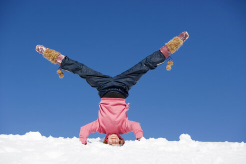 Austria, girl (10-11) doing headstand in snow - WESTF00700