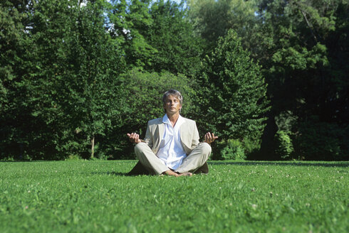 Mid adult man meditating in park, ground view - DKF00106