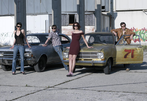 Young men and women standing by car - JL00107