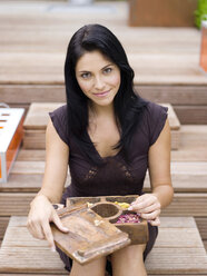 Woman holding spice box, smiling - WESTF01022