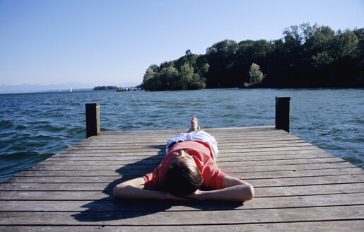 Young man relaxing on jetty, elevated view - WESTF01183