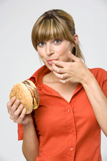 Young woman licking finger, holding hamburger, portrait, close-up - WESTF01319