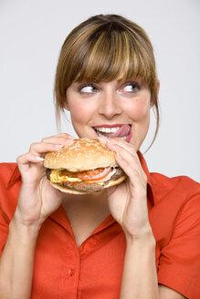Young woman holding hamburger, licking lips, close-up - WESTF01316