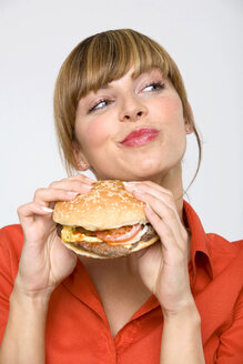 Young woman holding hamburger, sideways glance, close-up - WESTF01313