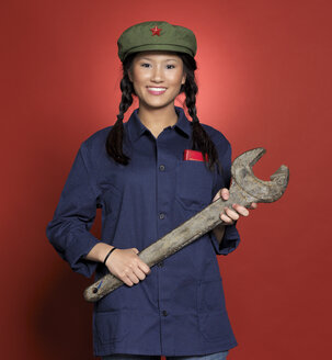 Young woman standing with spanner, smiling, portrait - JL00148