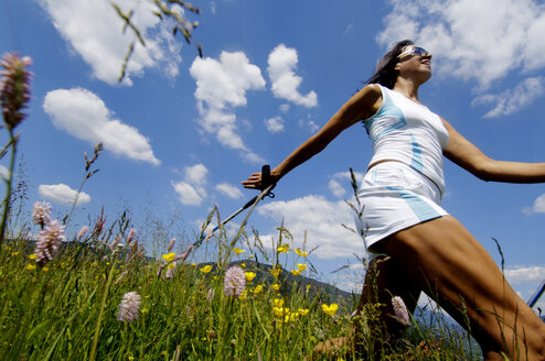 Young woman Nordic walking in meadow, Germany, low angle view - WESTF01436