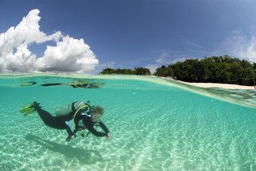 Philippines, Dalmakya Island, woman scuba diver in sea, underwater view - GNF00788
