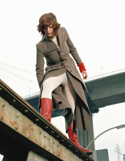 Woman standing on steel girder - DB00053