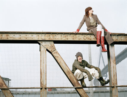 Man and woman sitting on steel girder - DB00050