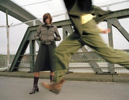 Woman standing on bridge, man running - DB00026