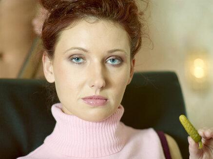 Woman, portrait, holding pickled cucumber - KM00180