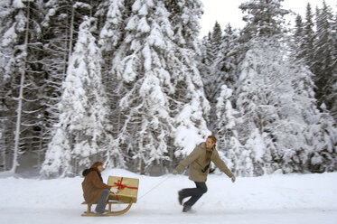 Young man pulling woman on sledge with Christmas gift - HHF00460