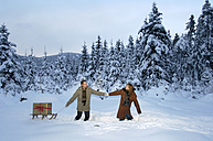 Young couple carrying Christmas gift on sledge in snow - HHF00457