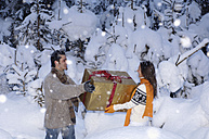 Young couple holding gift in snow - HHF00561