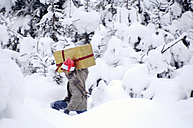 Young man walking in snow carrying gift - HHF00558