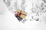 Young man walking in snow, carrying gift - HHF00552
