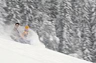 Young couple sliding on sledge, side view - HHF00543
