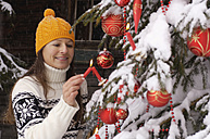 Woman decorating Christmas tree - HHF00537