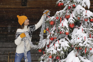 Young woman decorating Christmas tree in snow, smiling - HHF00534