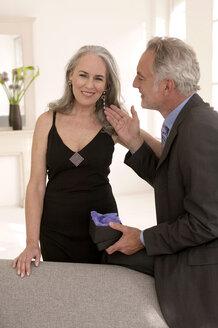 Mature men touching women's earring, smiling - WESTF01958