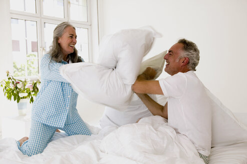 Mature couple having pillow fight on bed - WESTF01928