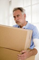 Mature man holding carton, looking away, close-up - WESTF01907