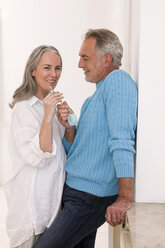 Mature couple holding key, smiling - WESTF01892