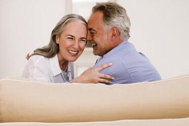 Mature couple embracing on sofa, smiling, close-up - WESTF01886