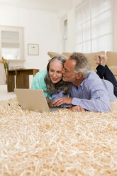 Mature couple lying on carpet with laptop, man kissing woman - WESTF01883