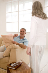 Mature couple in living room, man looking at woman, smiling - WESTF01865