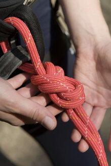 Woman knotting climbing rope, elevated view - WESTF02392