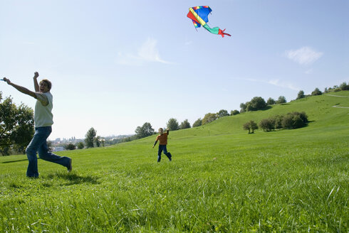 Father and son (4-7) flying kite in park - WESTF02273