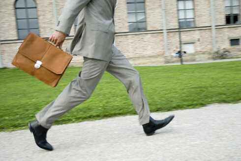 Businessman walking with briefcase, low section, (blurred motion) - WESTF02447