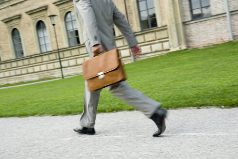 Businessman walking with briefcase, low section, (blurred motion) - WESTF02444