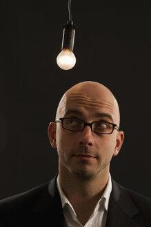 Young man standing under bulb, portrait - LD00165