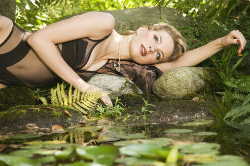 Young woman lying near pond - AB00047