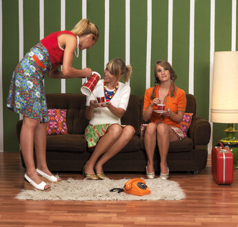Young women having coffee in living room - JL00188