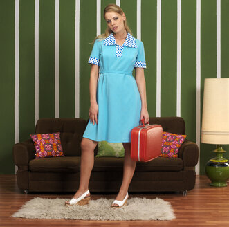 Woman with suitcase standing in front of sofa - JL00167