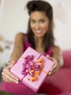 Teenage girl (16-17) holding gift, close-up - KMF00432