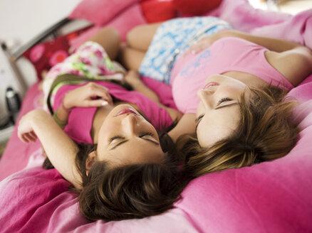 Two teenage girls lying on bed - KMF00407