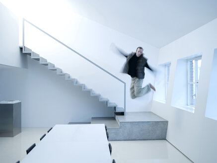 Young man jumping in excitement - KM00483