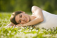 Germany, Bavaria, Munich, Young woman lying in meadow, smiling, portrait - KMF00256