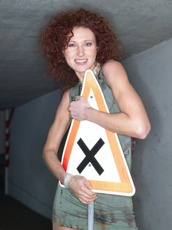 Young woman holding traffic sign, smiling, portrait - KM00294