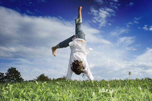 Girl (7-9) doing handstand in meadow, rear view - LDF00346
