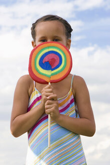 Girl (7-9) holding giant lollipop in front of face, close-up, portrait - LDF00331