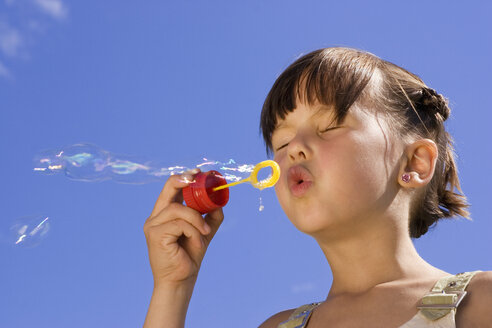 Girl (7-9) blowing soap bubbles, eyes closed, close-up - LDF00319