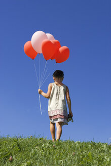 Girl (7-9) holding bunch of ballons, rear view - LDF00292