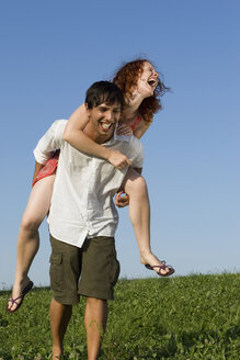 Man giving woman piggyback in meadow, laughing - LDF00244