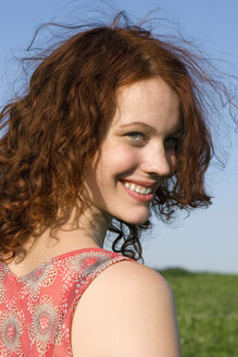 Young woman standing in meadow, smiling, close-up, portrait - LDF00235