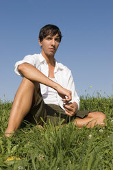 Young man sitting in meadow - LDF00223